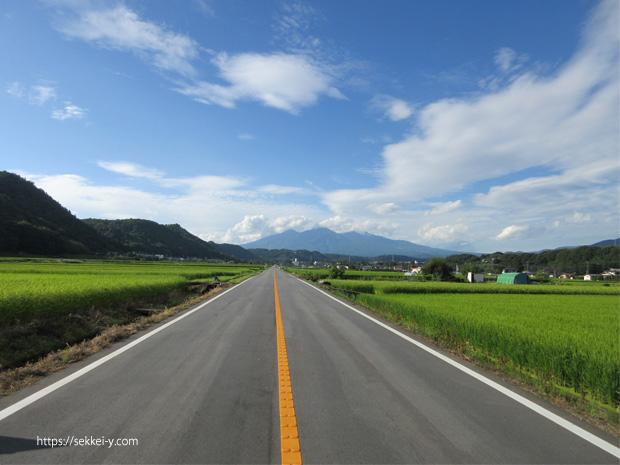 真っ直ぐに延びる道と八ヶ岳と稲穂